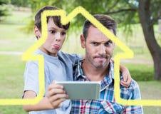 Papa et fils prenant un selfie dehors contre le contour de maison à l'arrière-plan photos stock