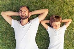 Papa et fils se reposant dehors Image libre de droits