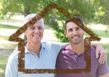 Papa et fils se tenant ensemble en parc avec le contour de maison image stock