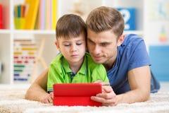 Papa et fils websurfing sur le comprimé numérique à la maison photos stock