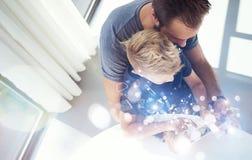Papa et petit garçon jouant ensemble sur le comprimé de PC d'ordinateur nomade, se reposant dans la maison moderne L'enfance rêve Photos libres de droits