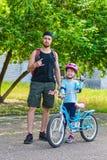 Papa et petite fille dans un casque rose et avec le vélo, jour du ` s de père Photographie stock