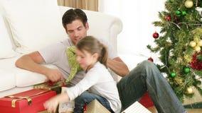 Papa et petite fille jouant avec des cadeaux de Noël banque de vidéos