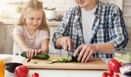 Papa et petite fille préparant la salade Photos libres de droits