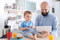 Papa et son petit fils à l'aide des dispositifs pendant le petit déjeuner photographie stock libre de droits