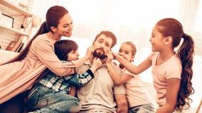 Papa fatigué avec la famille mignonne heureuse ennuyant photos libres de droits
