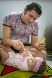 Papa feeds child with spoon. Image of young dad Royalty Free Stock Photography