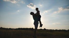 Papa heureux jetant son petit garçon dans le ciel à la nature Silhouettes du père et du fils jouant sur le pré à clips vidéos