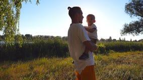 Papa heureux tenant dans des mains son fils avec les cheveux blonds au parc un jour ensoleillé Jeune père et sa dépense de petit  banque de vidéos