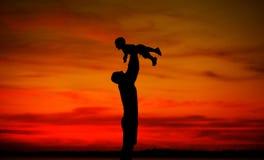 Papa jetant son bel enfant en l'air Photos stock