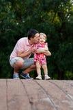 Papa met dochter op houten brug in park Stock Afbeelding