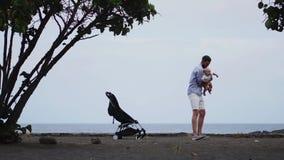 Papa met een baby op het strand met een wandelwagen stock videobeelden