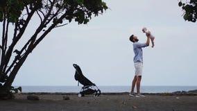 Papa met een baby op het strand met een wandelwagen stock video