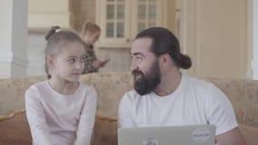 Papa met leuke dochter en laptop zitting in de woonkamer op de laag en het spreken over iets grappig op stock video