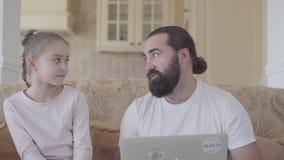 Papa met leuke dochter en laptop zitting in de woonkamer op de laag en het spreken over iets stock videobeelden