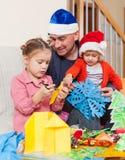 Papa met twee dochters die ambachten maken stock afbeelding