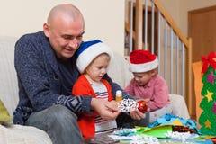 Papa met twee dochters die ambachten maken stock fotografie