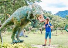 Papa met weinig dochter dichtbij grote groene dinosaurus in het park op een zonnige dag Yang Bay, Vietnam royalty-vrije stock afbeeldingen