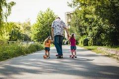 Papa met zijn dochters op een skateboard en een autoped Stock Foto's