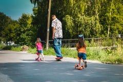 Papa met zijn dochters op een skateboard en een autoped Royalty-vrije Stock Foto
