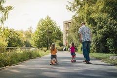 Papa met zijn dochters op een skateboard en een autoped Stock Foto