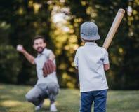 Papa met zoons speelhonkbal stock foto's