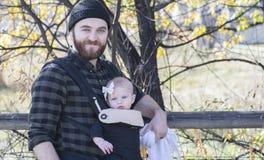 Papa millénaire avec le bébé dans la marche extérieure de transporteur images stock