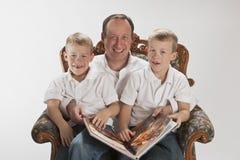 Papa moderne affichant un livre avec des garçons de 6 années Image stock