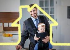 Papa portant son bébé dans le transporteur de bébé contre le contour de maison à l'arrière-plan image stock