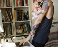 Papa portant son bébé et occupé utilisant l'ordinateur portable d'ordinateur Photo stock