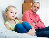 Papa sérieux et petite fille se disputant à l'intérieur photo stock