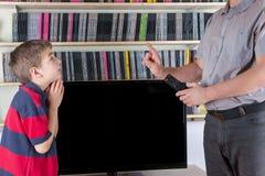 Papa strict avec ne pas laisser à télécommande de TV regardant la TV f image libre de droits