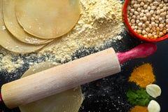 Papadums ha fatto dalla farina di grammo, dal matterello di legno e dalle spezie Immagine Stock