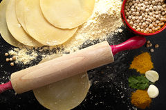 Papadums made from gram flour, wooden rolling pin and indian spi Royalty Free Stock Photo