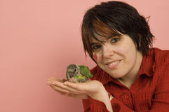 Papagaio bonito do bebê da terra arrendada da mulher foto de stock royalty free