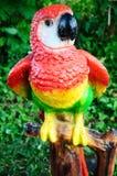 Papagaio cerâmico na madeira no jardim foto de stock