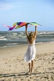Papagaio da terra arrendada da menina na praia. Fotos de Stock Royalty Free