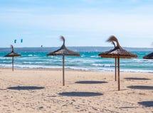 Papagaios e parasóis da palha em parasóis do forte vento e da palha Fotos de Stock
