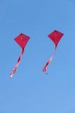 Papagaios vermelhos que voam em um céu azul Fotografia de Stock Royalty Free