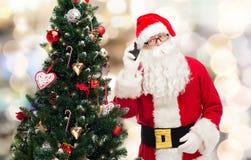 Papai Noel com a árvore do smartphone e de Natal Foto de Stock Royalty Free