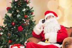 Papai Noel com a árvore do smartphone e de Natal Fotos de Stock