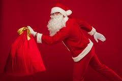 Papai Noel com o saco grande no fundo do vermelho dos vidros do ombro Imagens de Stock
