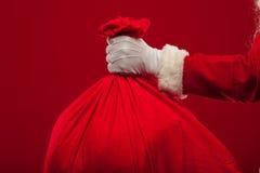 Papai Noel com o saco grande no fundo do vermelho dos vidros do ombro Fotos de Stock