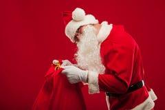 Papai Noel com o saco grande no fundo do vermelho dos vidros do ombro Fotos de Stock Royalty Free