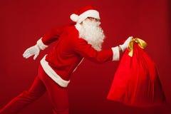 Papai Noel com o saco grande nos vidros do ombro vermelhos Foto de Stock Royalty Free