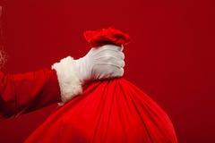 Papai Noel com o saco grande nos vidros do ombro vermelhos Fotografia de Stock
