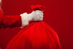 Papai Noel com o saco grande nos vidros do ombro vermelhos Foto de Stock