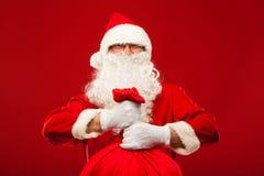 Papai Noel com o saco grande nos vidros do ombro vermelhos Fotografia de Stock Royalty Free