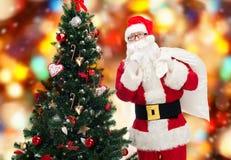Papai Noel com saco e árvore de Natal Foto de Stock