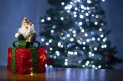 Papai Noel e árvore vermelha brilhante da caixa de presente e de Natal no fundo foto de stock
